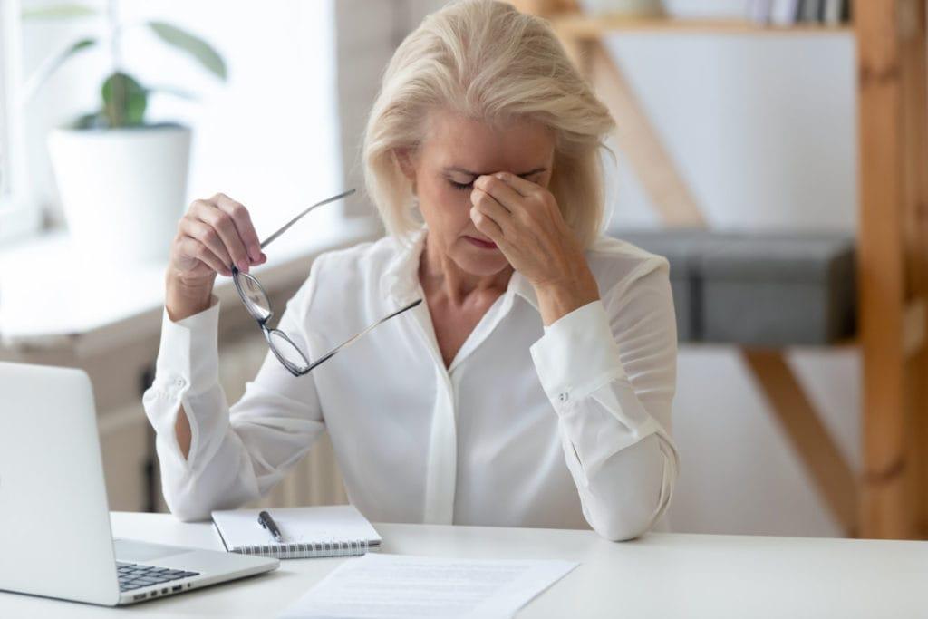 Frau am PC mit Brillen der Hand