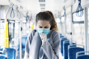 Frau im Bus hustet