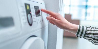 Hausfrau bedient Wäschetrockner